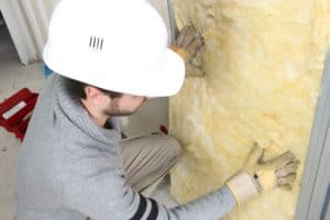 a man replacing insulation that was infested by termites with fiberglass insulation. used to show how termites love to use your insulation to hide in your phoenix home and protect themselves. call budget brothers termite and pest elimination for help with your termites.