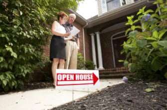 Couple standing in front of a house with an Open House sign looking at documents.